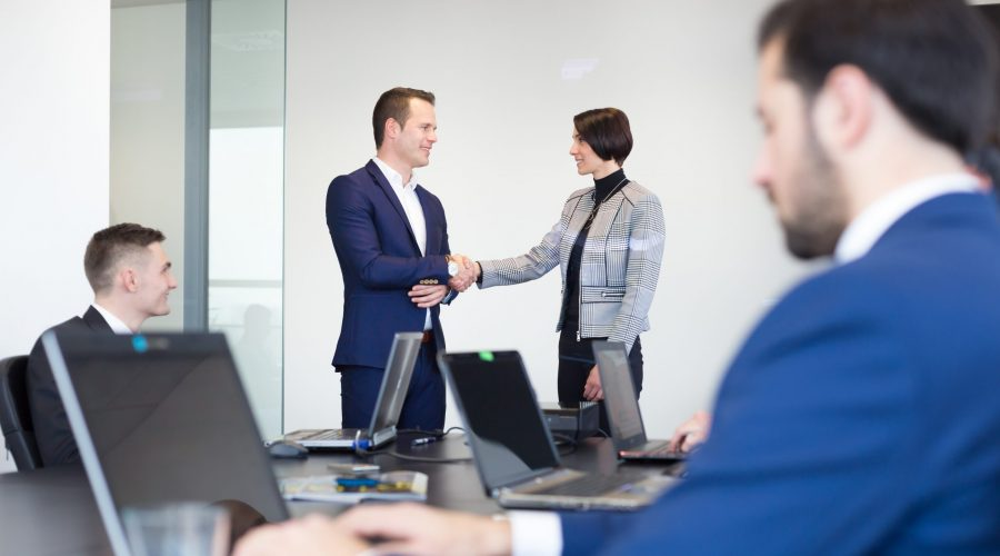 Sealing a deal. Business people shaking hands, finishing up meeting in corporate office. Businessman working on laptop in foreground. Business and entrepreneurship concept.