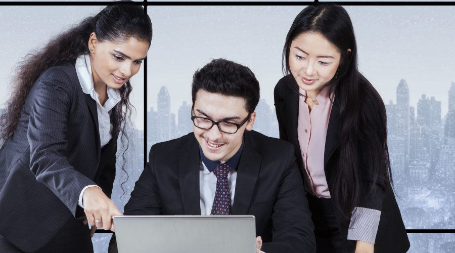 Portrait of young businesswoman showing document on laptop to her partners in the office