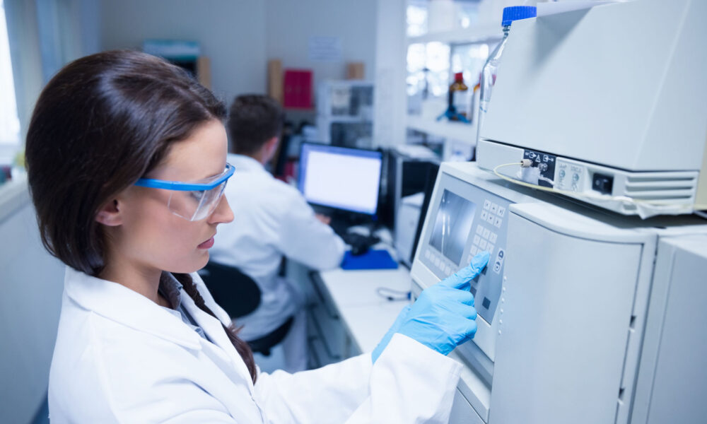 Young chemist using the machine in the laboratory