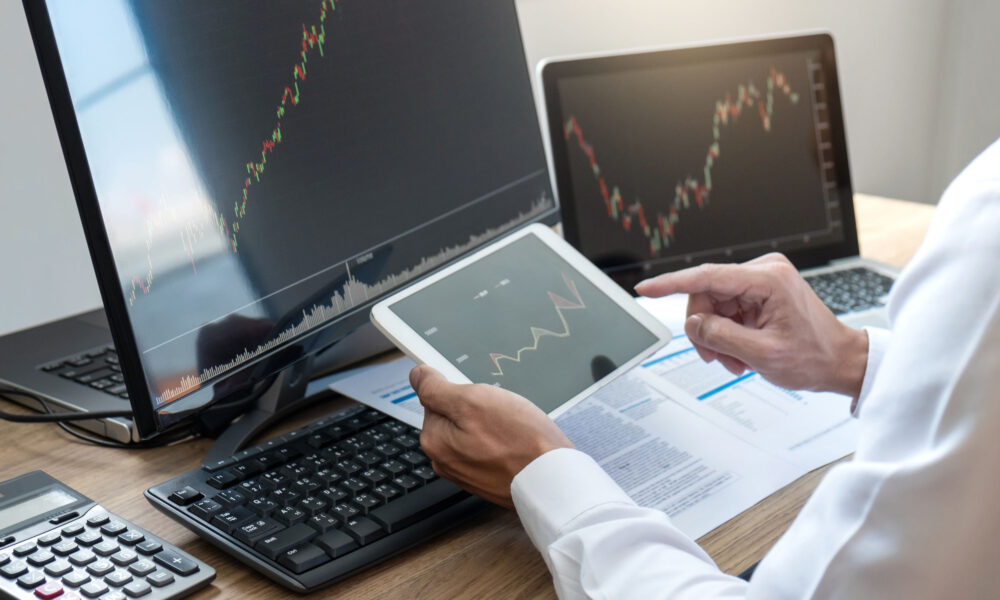 Stock exchange market concept, stock broker looking at graph working and analyzing with display screen, pointing on the data presented and deal on a exchange, Businessman trading stocks online.